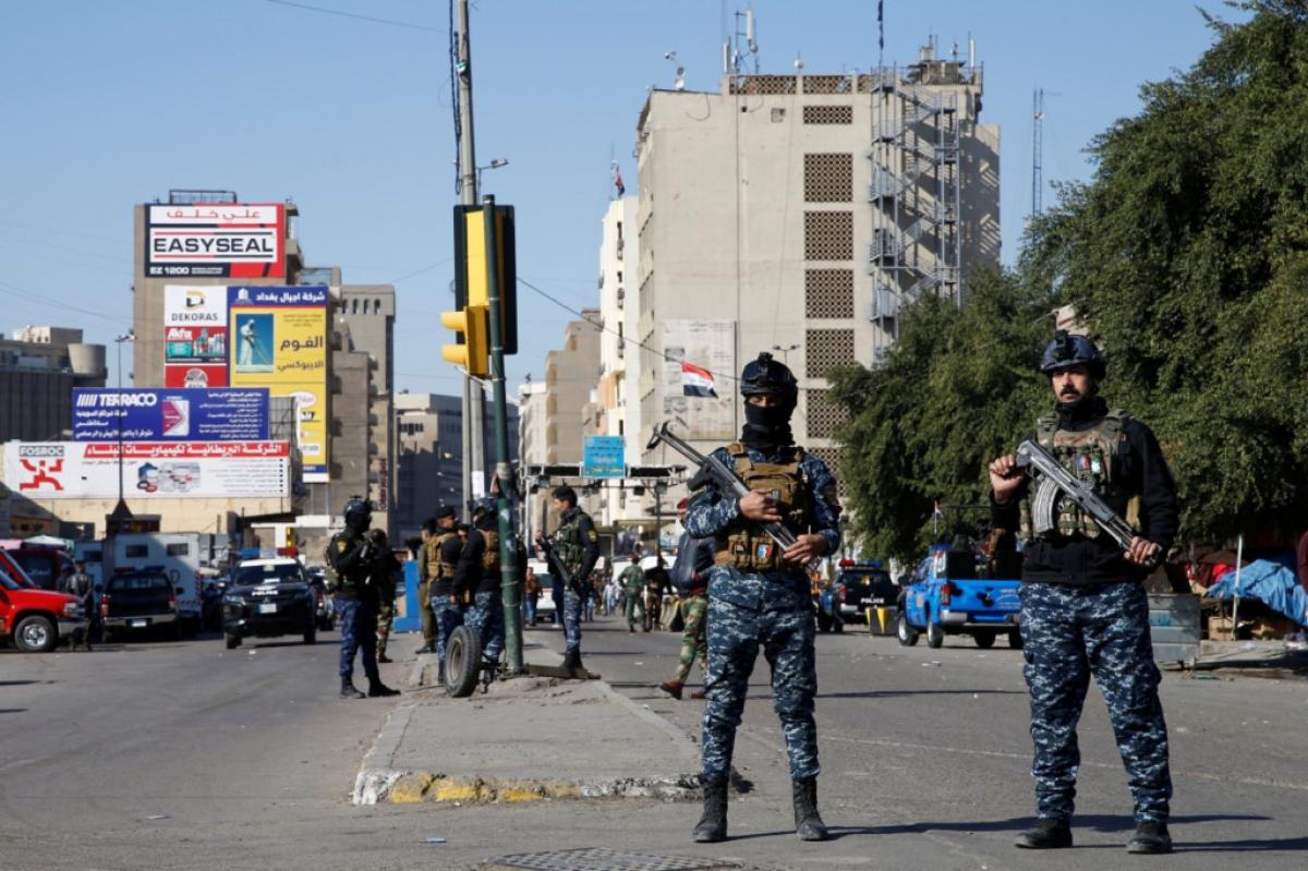 Các thành viên trong lực lượng an ninh Iraq canh gác tại khu chợ trung tâm ở thủ đô Baghdad, Iraq sau một vụ đánh bom liều chết do IS tiến hành. Ảnh: Reuters