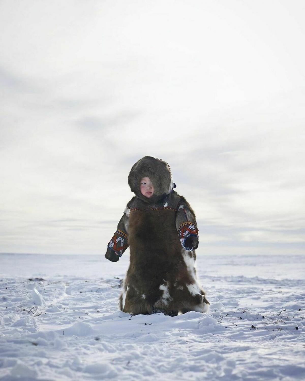 Bộ quần áo bằng lông thú của em bé giữa mùa đông tuyết trắng ở nước Nga.