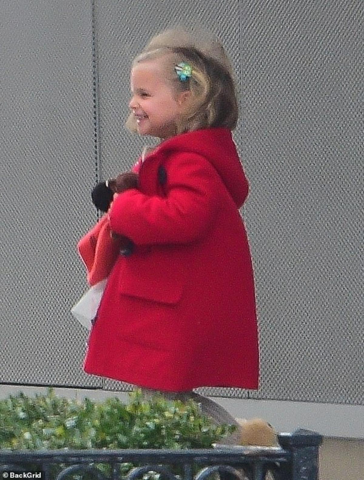 Cô bé xinh xắn với mái tóc cài nơ hoa, áo khoác đỏ vừa vặn.