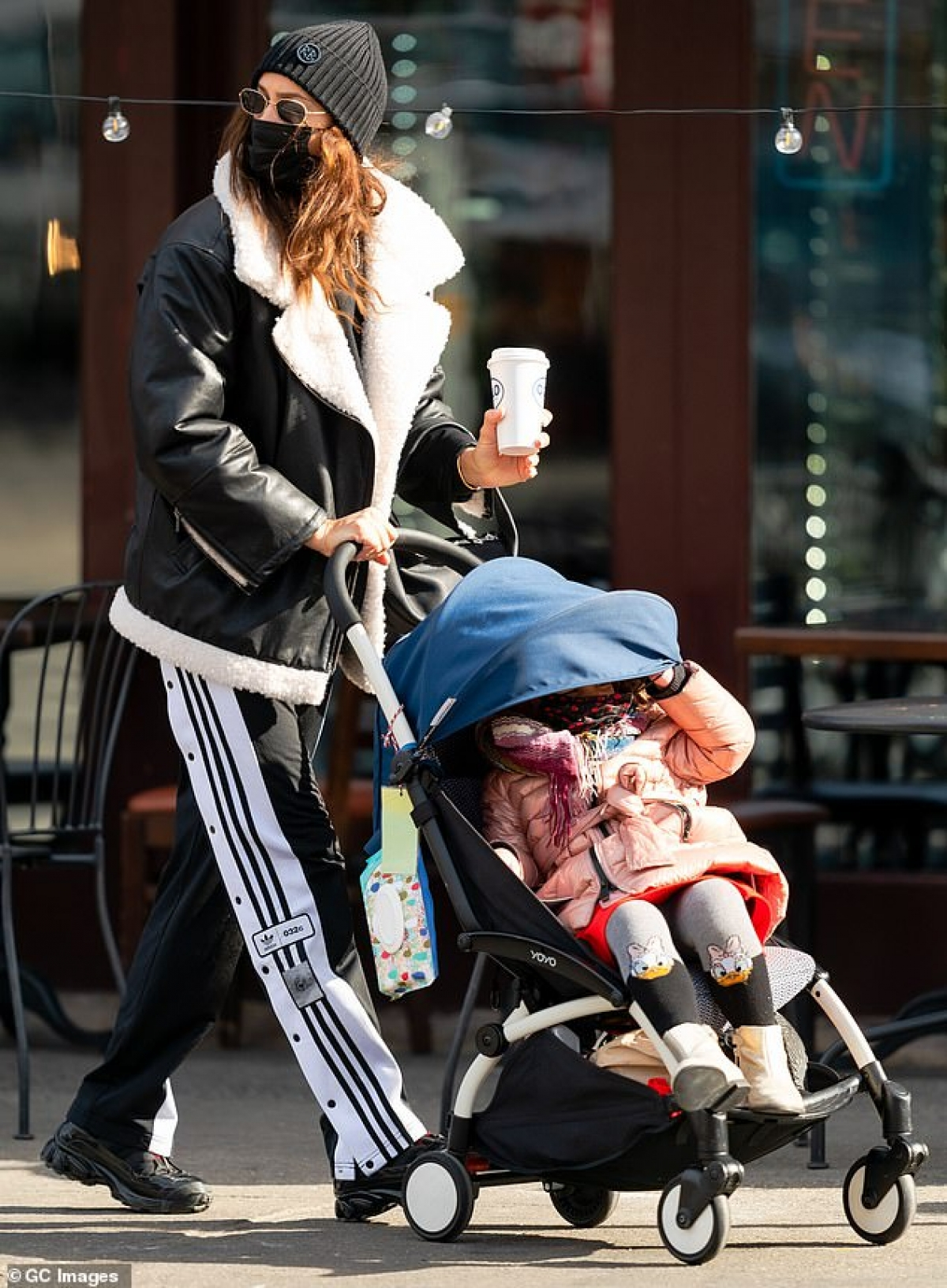 Siêu mẫu Nga diện set đồ màu đen khỏe khoắn, cầm theo ly cafe nóng hổi.