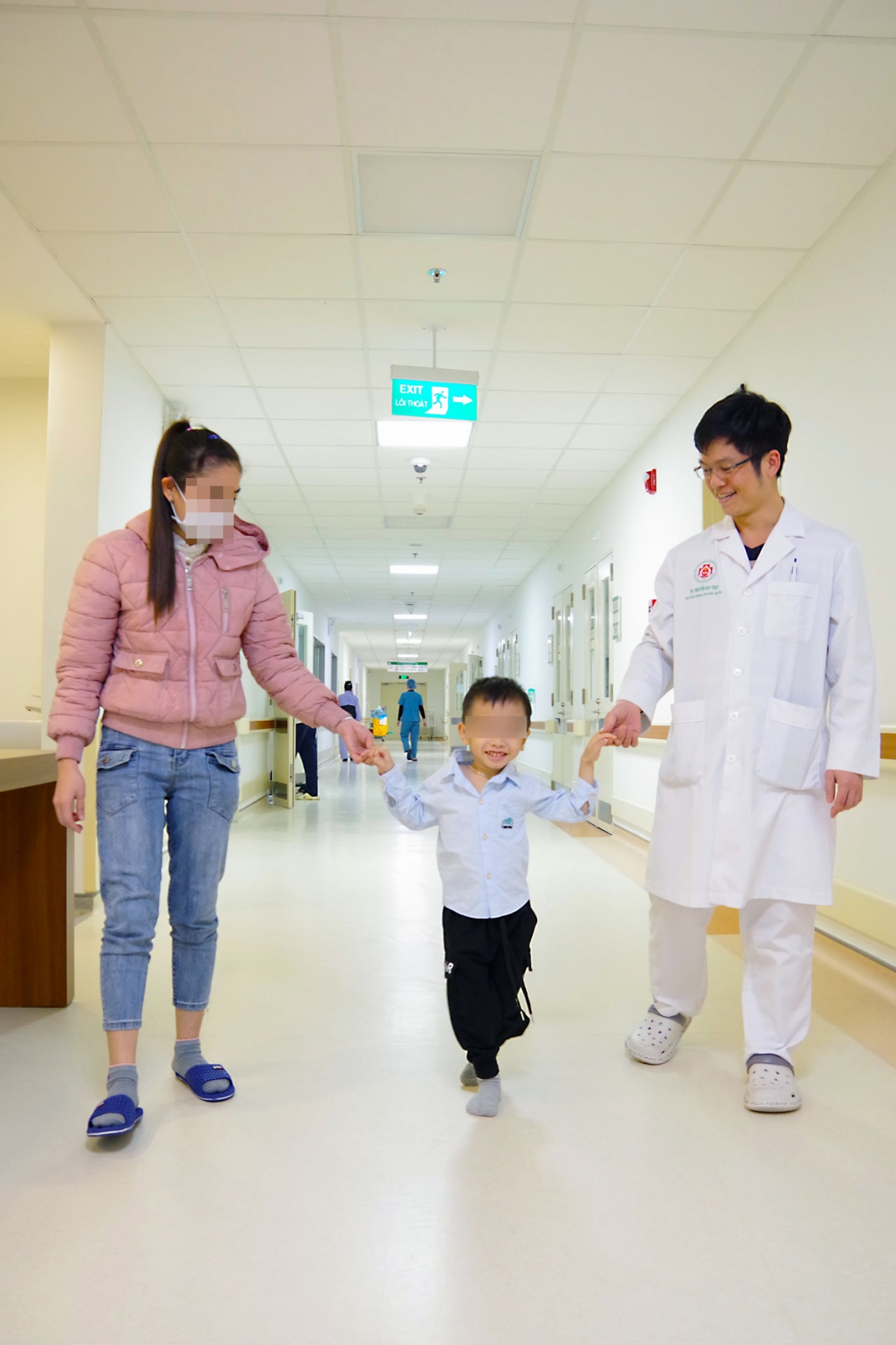Với nụ cười tươi trên môi, sau ca phẫu thuật thành công, bé B.Đ đã có thể bước những bước chân tự tin cùng với mẹ và bác sĩ Nguyễn Duy Thụy. (Ảnh: BVCC)