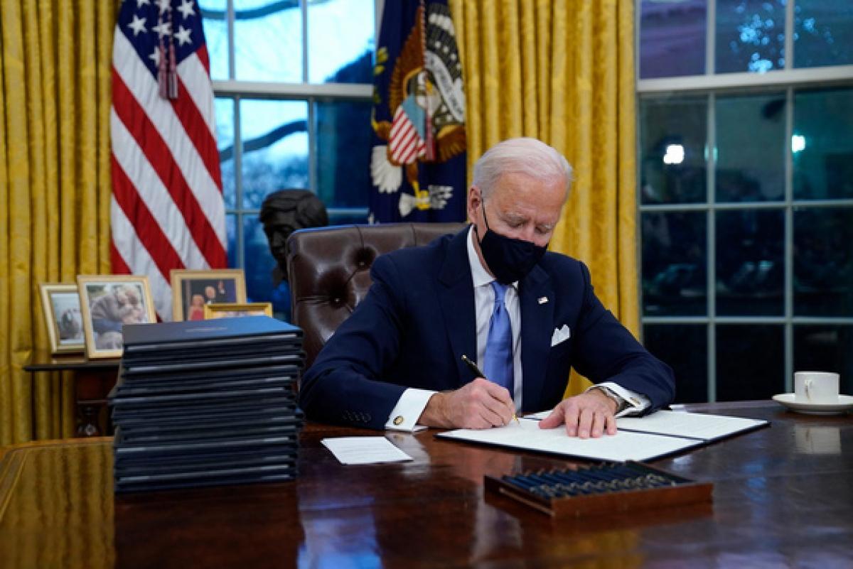 Tổng thống Biden ký sắc lệnh hành pháp trong phòng Bầu Dục ngay sau lễ nhậm chức. Ảnh: AP