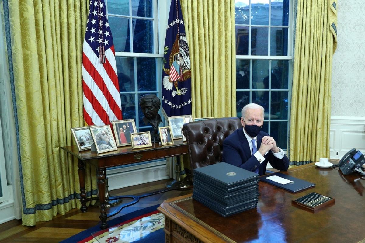 Ông Biden ngồi trên một chiếc ghế da màu nâu sẫm, phía sau là các bức ảnh gia đình. Ảnh: Washington Post.
