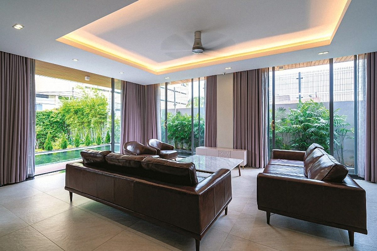 Phòng khách nằm ở phía trước ngôi nhà với những ô cửa lớn mở ra sân vườn với những khoảng xanh mát mắt.