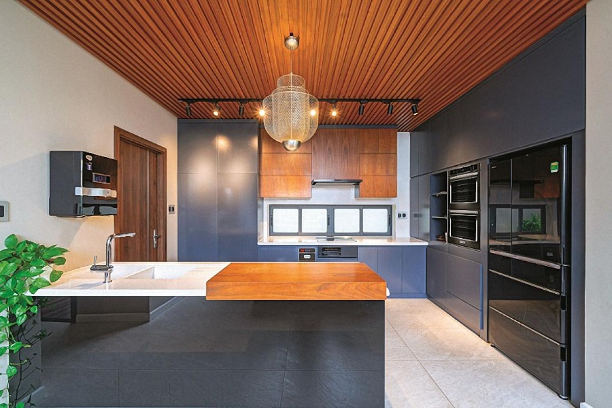Khu bếp nấu tiện nghi được kết hợp các loại thiết bị, vật liệu hiện đại với chất liệu gỗ truyền thống mang lại vẻ ấm áp.