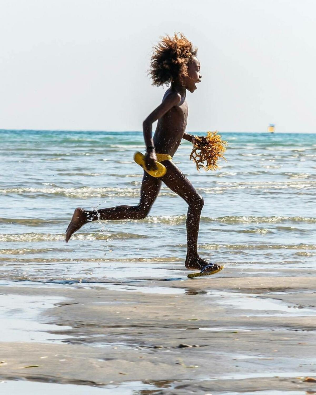 Cậu bé vui sướng chạy trên bãi biển ở Madagasca.