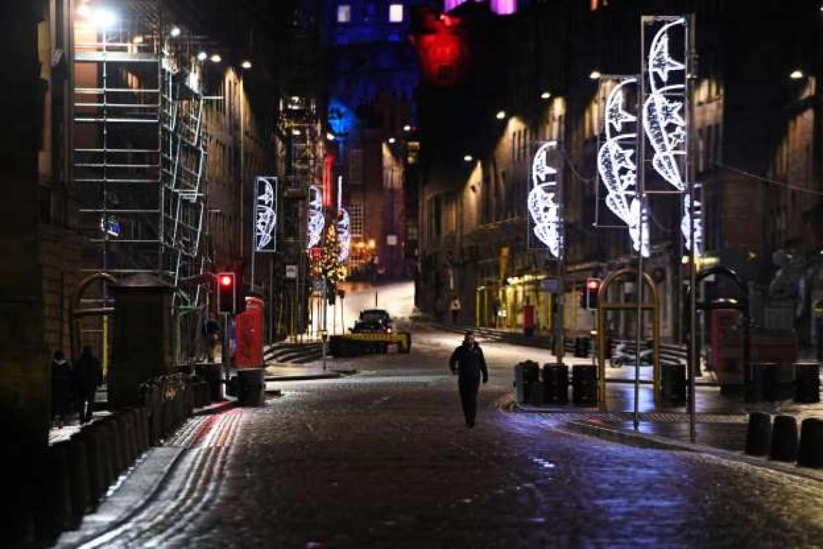 Một người đi bộ một mình ở Edinburgh đêm 31/12 giữa bối cảnh các nhà chức trách Scotland khuyến cáo mọi người nên ở nhà để hạn chế dịch Covid-19 lây lan.
