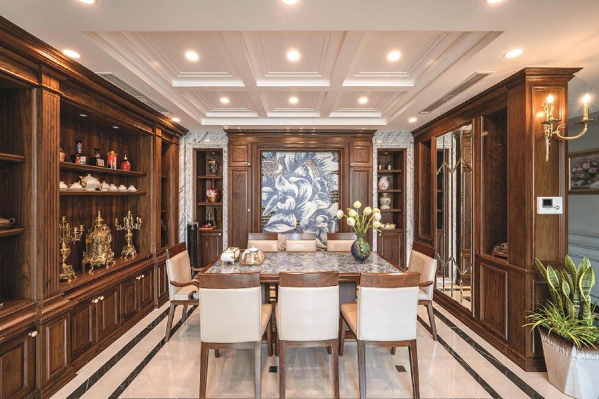 Tầng 1 là không gian phòng khách, phòng ăn và bếp cùng phòng ngủ của con gái. Phòng ăn được thiết kế với chất liệu gỗ ấm áp kế bên phòng khách. Các diện tường được tận dụng làm tủ để đồ.