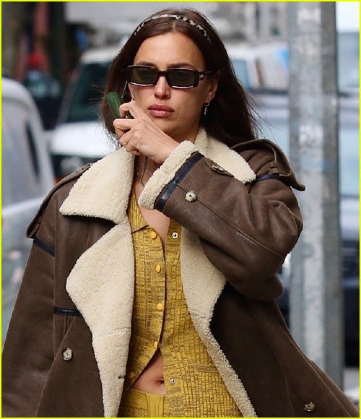 Siêu mẫu Nga diện trang phục màu vàng nổi bật phối cùng áo khoác dáng dài sang chảnh.