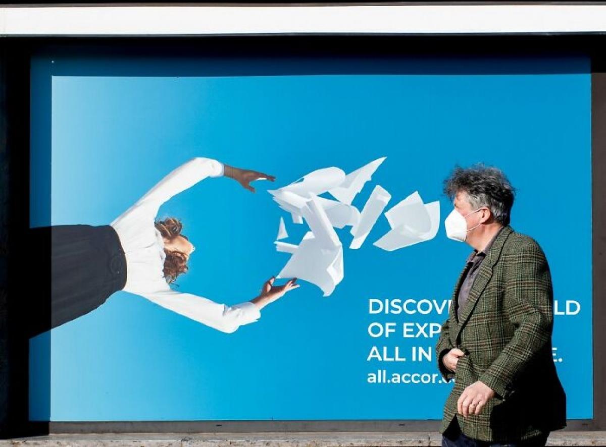 Chiếc khẩu trang màu trắng của người đàn ông phối hợp ăn ý với bức hình quảng cáo.