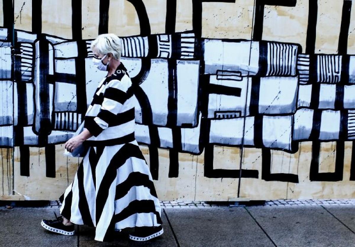 Bộ váy của người phụ nữ ăn ý với hoạ tiết trên bức tường.