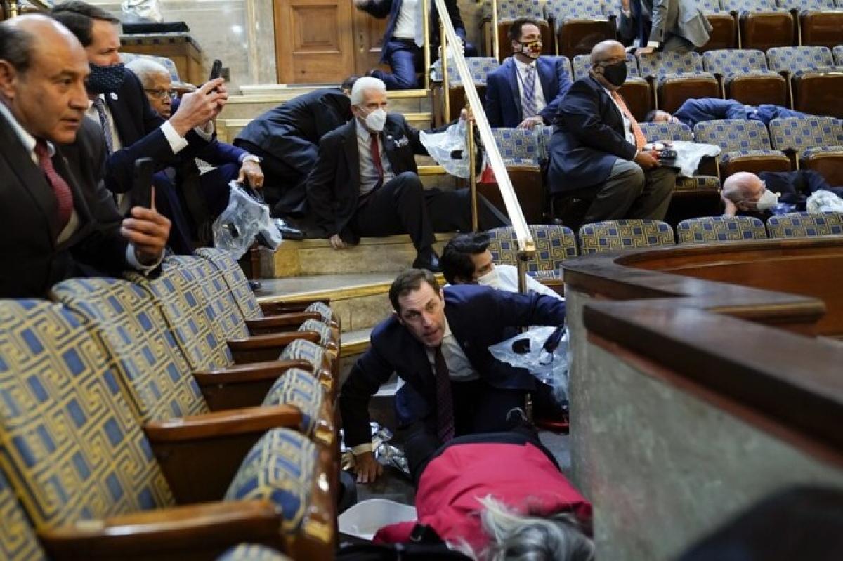 Các nghị sĩ núp xuống ghế khi người ủng hộ Trump xông vào Điện Capitol ngày 6/1. Ảnh:AP.