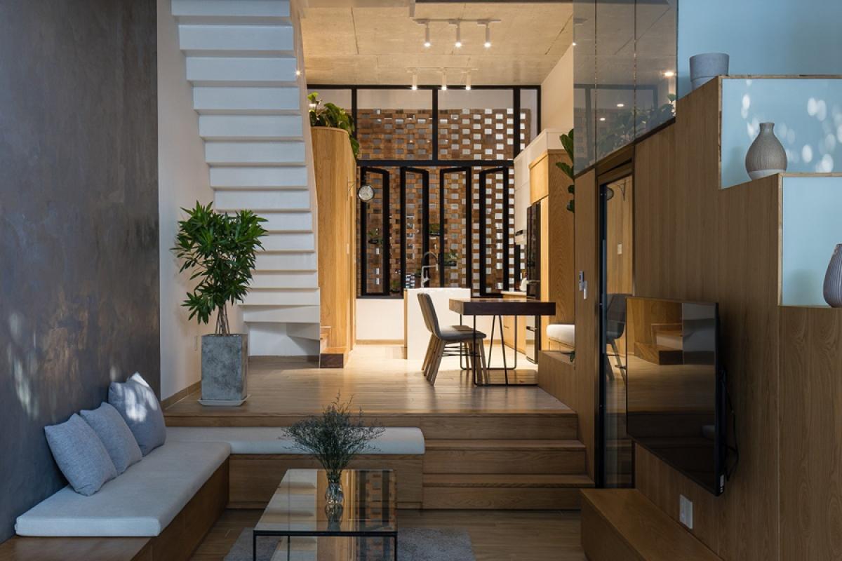 Tầng 1 công trình được sử dụng để kinh doanh, từ tầng 2 trở lên là nhà ở gia đình. Tầng 2 là một không gian xuyên suốt phòng khách và phòng ăn – bếp nấu. Cầu thang được thiết kế nép sang một bên để không gian rộng mở. Phía cuối nhà có một giếng trời cũng được xây bao che bằng tường hoa.
