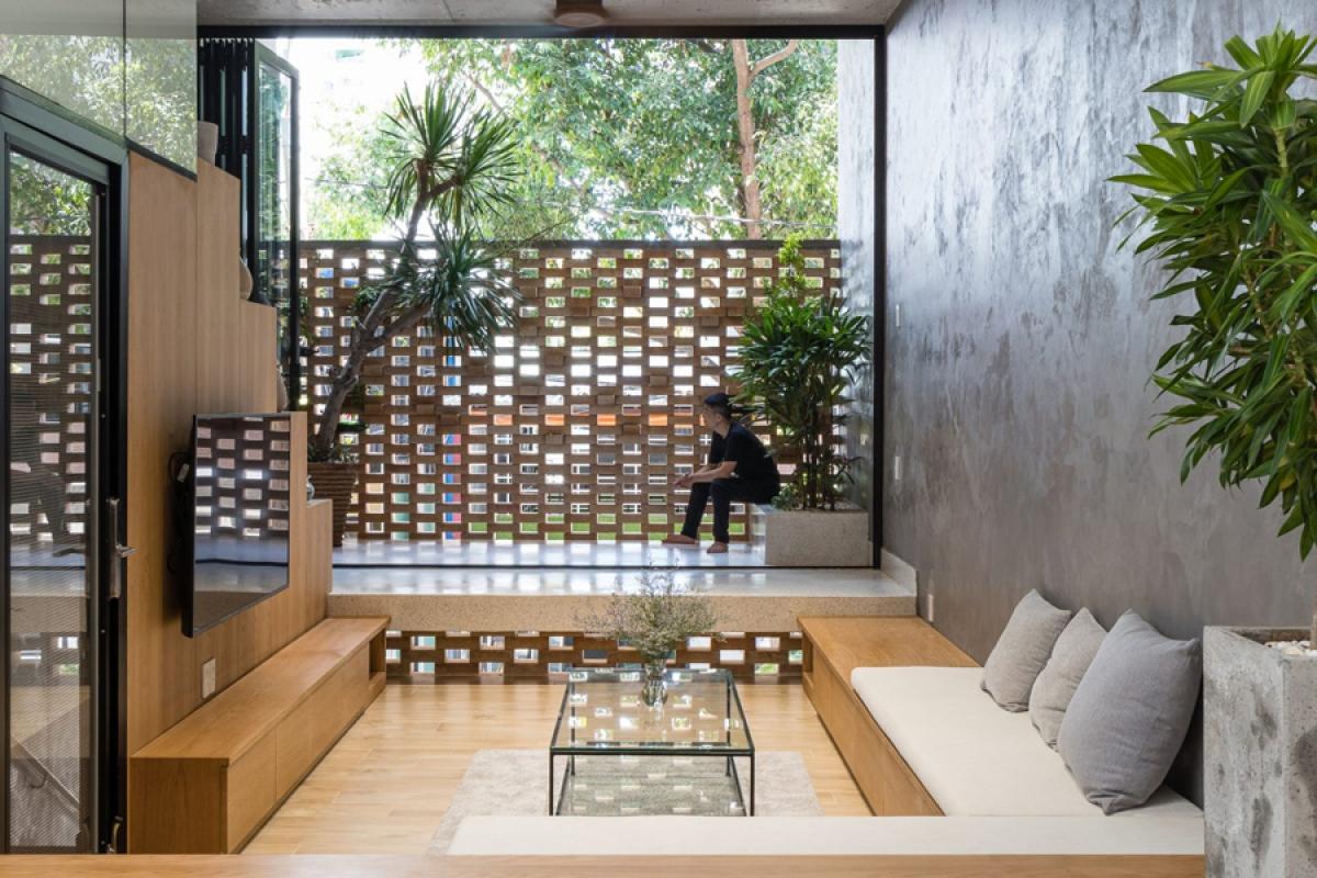 Không gian phòng khách tiếp xúc với phía trước qua lớp áo tường hoa tạo cảm giác kín đáo mà vẫn thông thoáng. Hệ kết cấu bao che này ngăn được 70% bức xạ nhiệt lên bề mặt bên trong công trình.