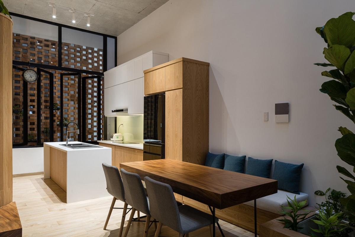 Khu vực bếp – ăn tiếp giáp với giếng trời phía sau nên đảm bảo luôn thông thoáng. Đồ nội thất được thiết kế với phong cách hiện đại, đơn giản.