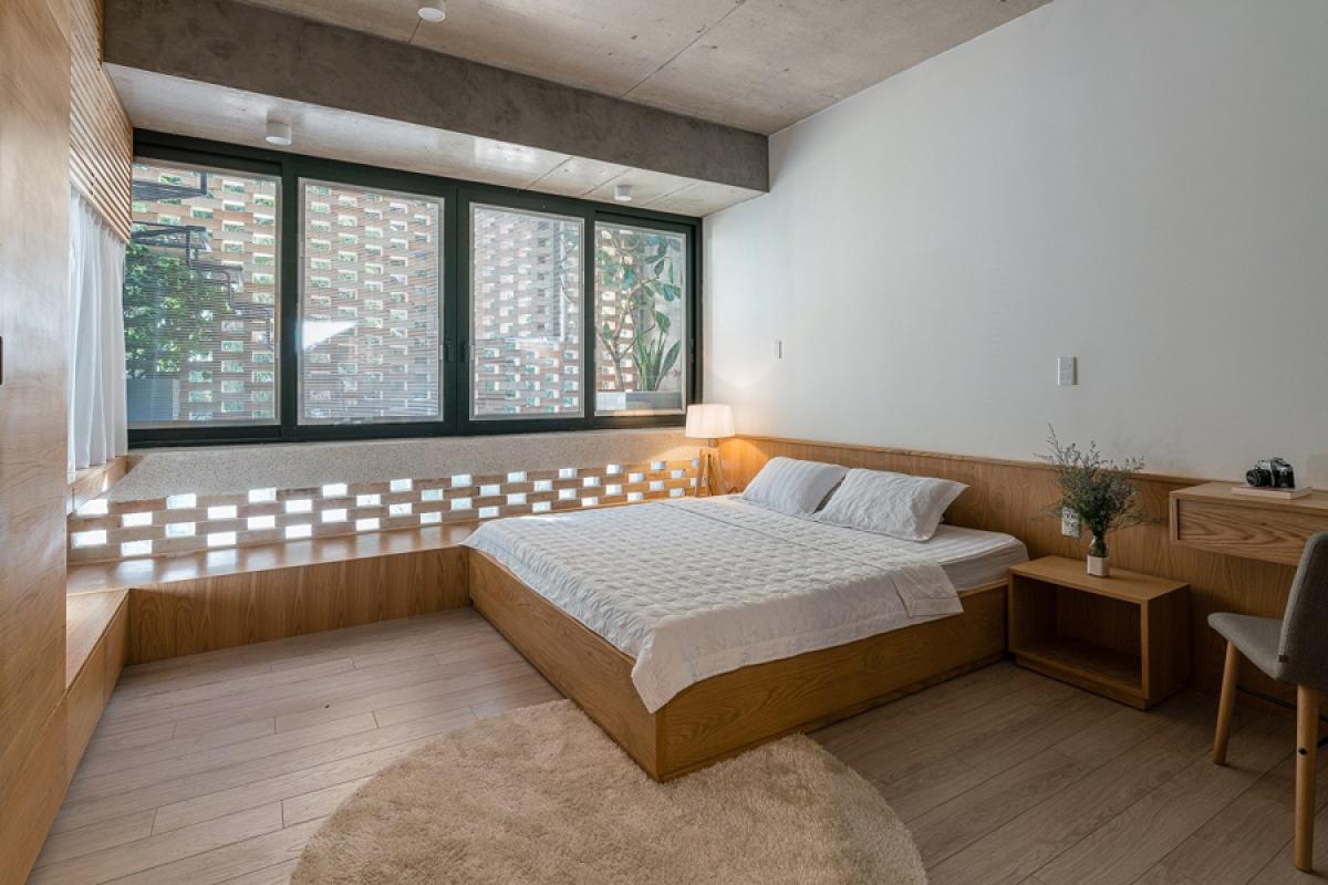 Phòng ngủ chính nằm ở phía trước tầng 3, cũng được ngăn với bên ngoài bằng 2 lớp áo. Nội thất bằng gỗ sáng màu, đơn giản cho cảm giác hiện đại, thanh lịch, nhã nhặn.