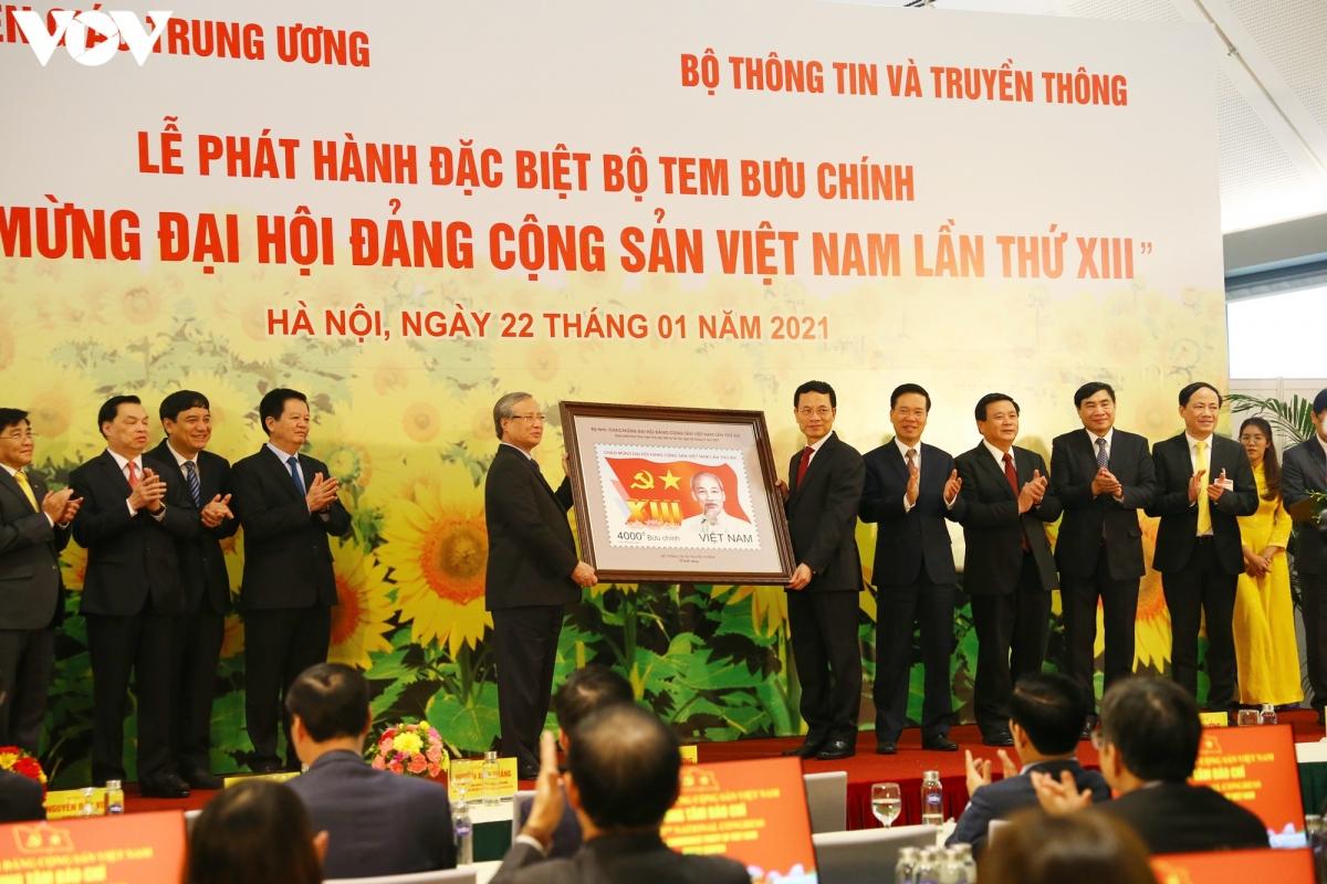 Bộ trưởng Bộ Thông tin - truyền thông Nguyễn Mạnh Hùng (thứ hai bên phải) trao tặng Bộ tem đặc biệt mừng Đại hội Đảng XIII cho ông Trần Quốc Vượng - Ủy viên Bộ Chính Trị, Thường trực Ban Bí thư, Trưởng Tiểu Ban phục vụ Đại hội XIII.
