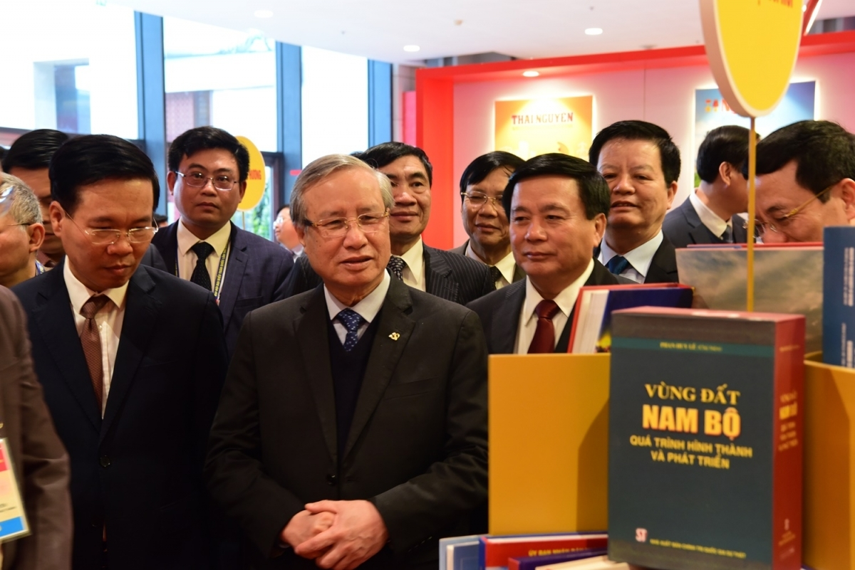 Politburo member and permanent member of the Party Central Committee's Secretariat Tran Quoc Vuong joins with Party leaders as they pay a visit to book stalls.