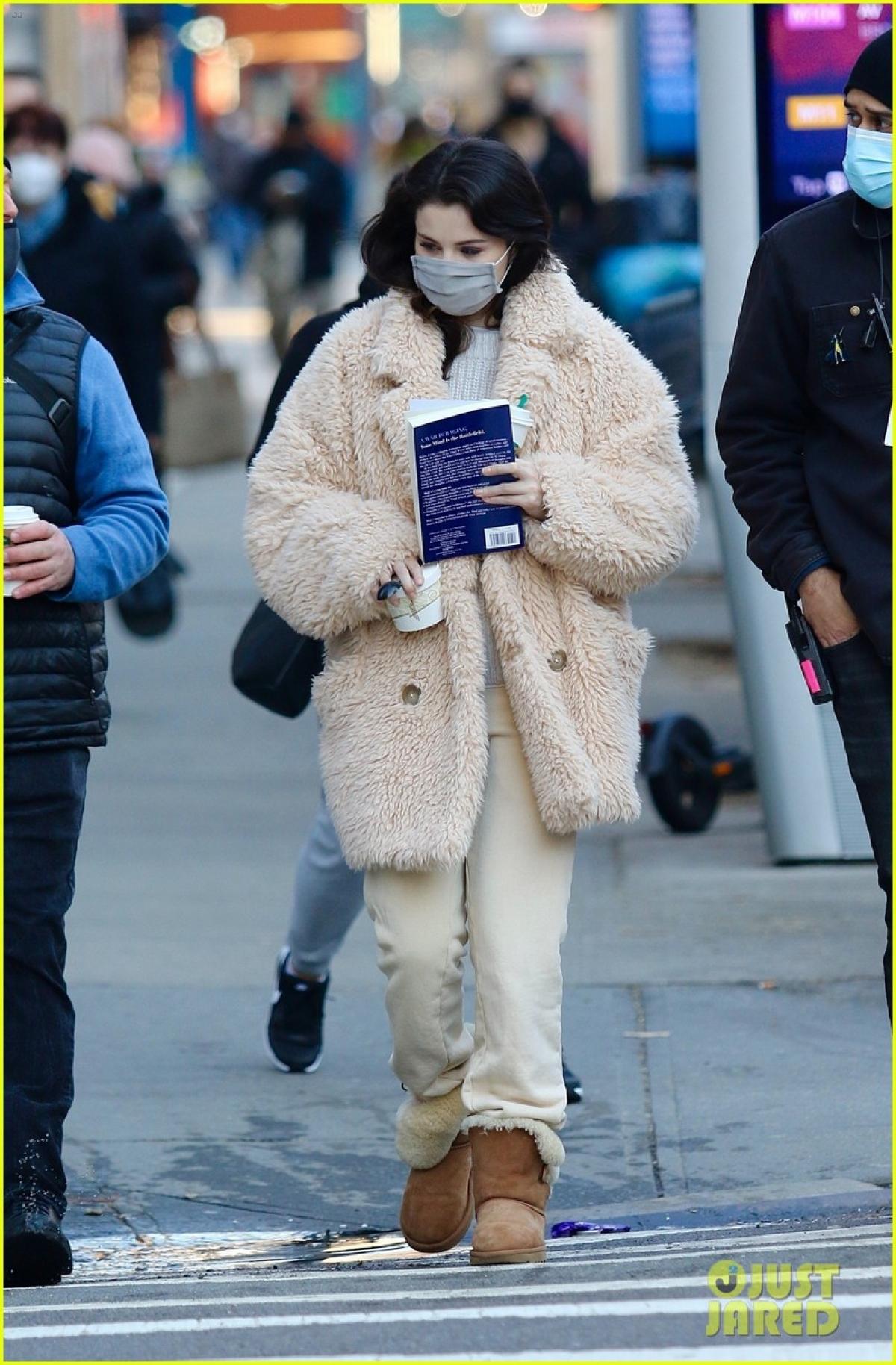 Nữ ca sĩ diện trang phục kín đáo, ấm áp và cầm theo cuốn sách sải bước trên phố.