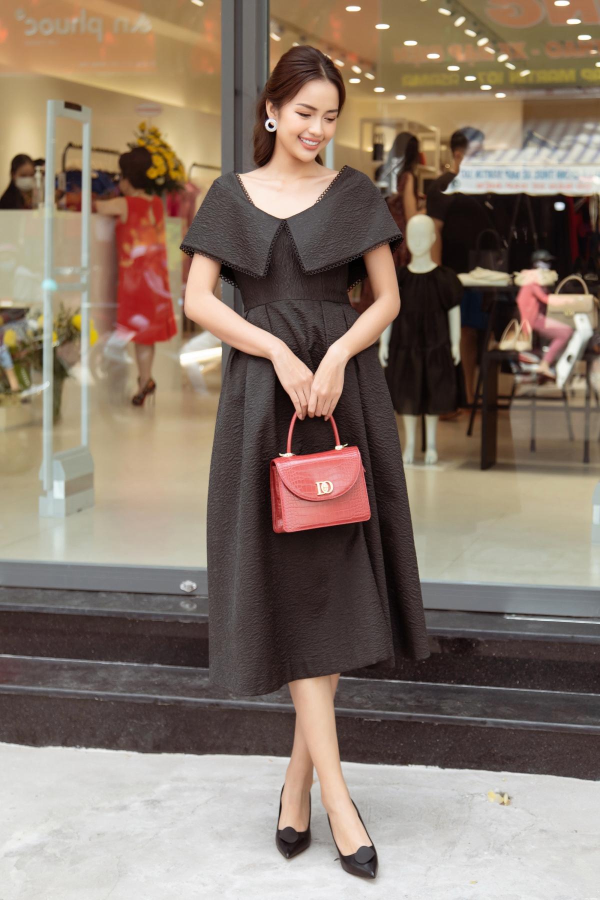 """Ngọc Châu bất ngờ """"đụng hàng"""" Lan Ngọc, nhưng với thiết kế có tông màu đen huyền bí. Người đẹp phối bộ váy cùng chiếc túi đỏ xinh xắn, nổi bật. Trong sự kiện, cô còn diện một bộ váy trắng xoè được điểm xuyết chi tiết nơ 3D độc đáo ngay phần cổ."""