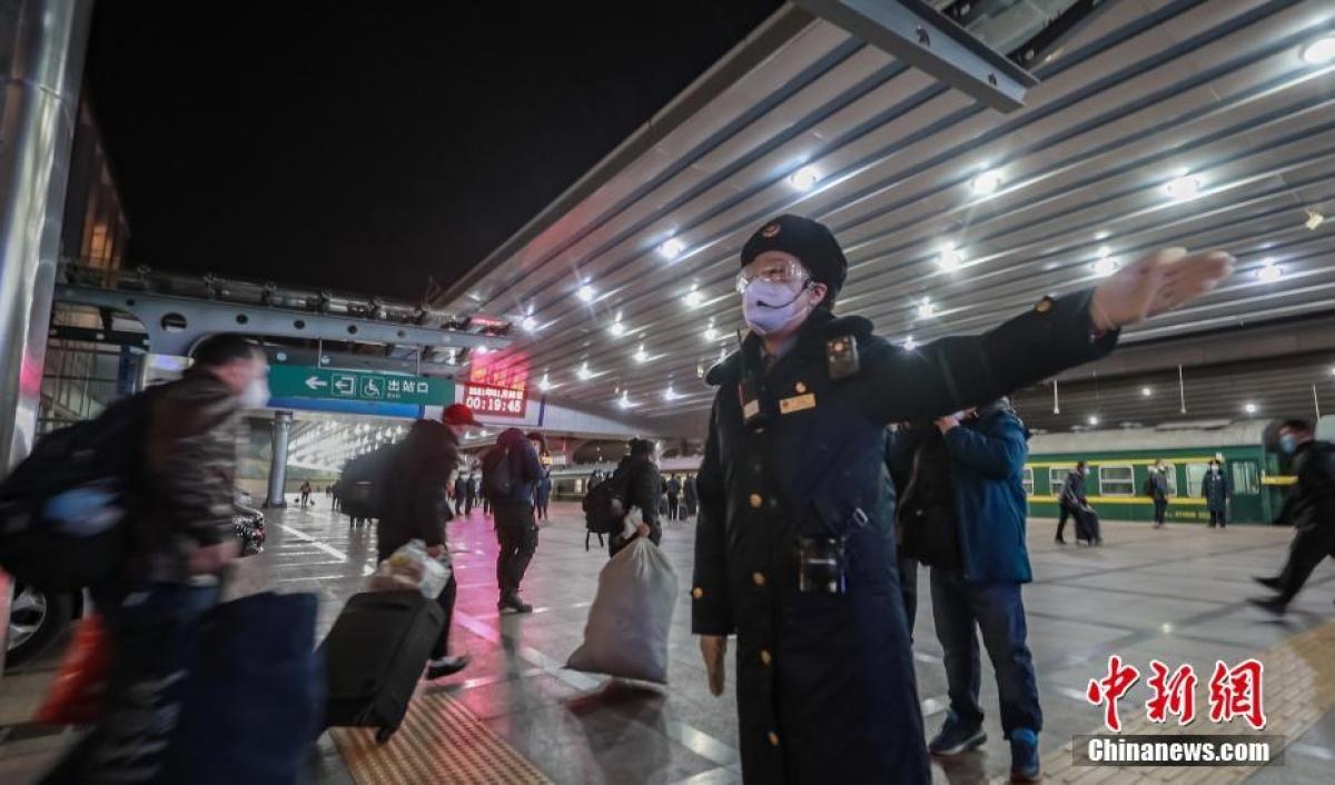 Nhân viên nhà ga hướng dẫn hành khách lên tàu. Áp lực đối với ngành đường sắt của Trung Quốc trong dịp này là rất lớn vì vừa phải đảm bảo yêu cầu phòng chống dịch vừa phải đảm bảo giao thông thông suốt.