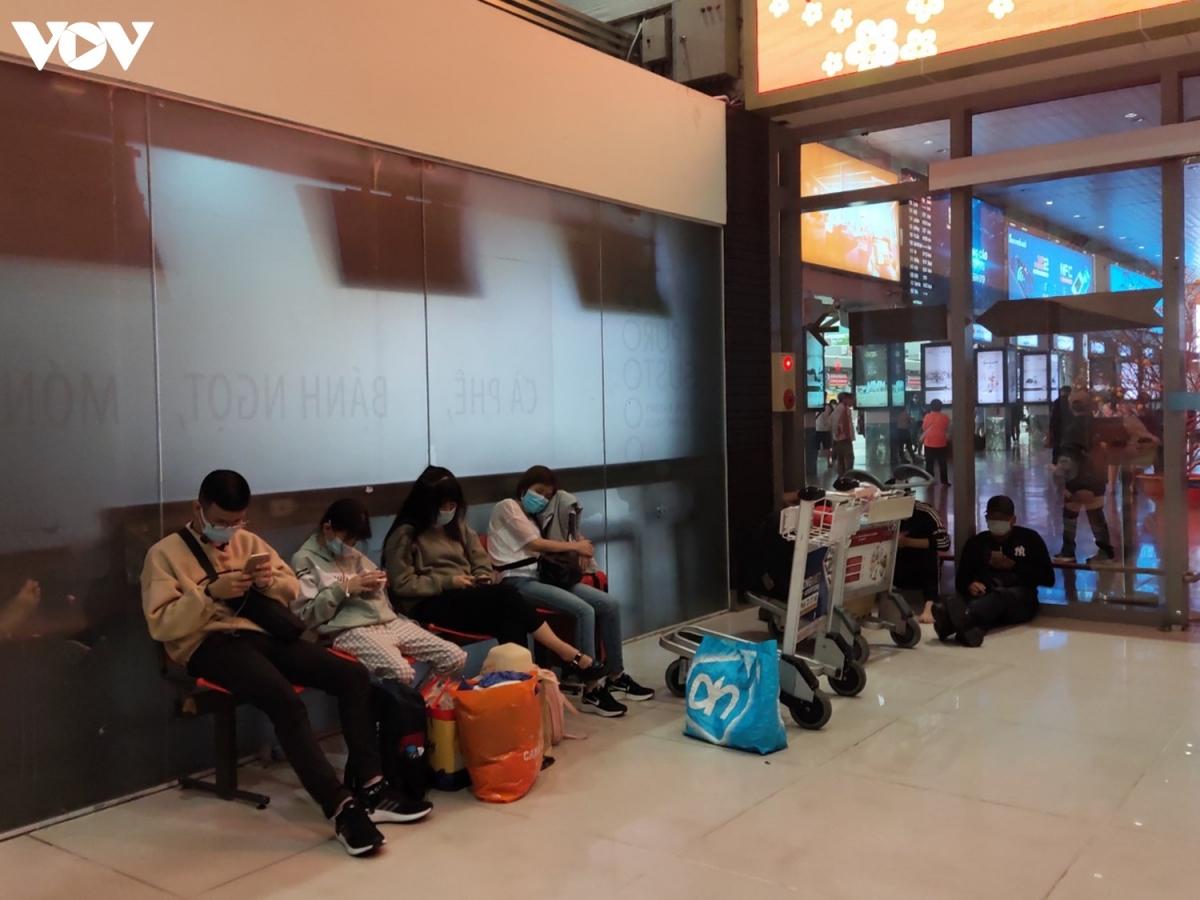 Một số hành khách ngồi vạ vật dưới nền hoặc tranh thủ ngủ tại các hàng ghế trong khu vực làm thủ tục chờ tới giờ bay. Người dân đều đeo khẩu trang để đảm bảo an toàn trước dịch bệnh Covid-19. Nhiều người cẩn thận mặc áo bảo hộ, đeo găng tay, đội mũ che kín mặt.