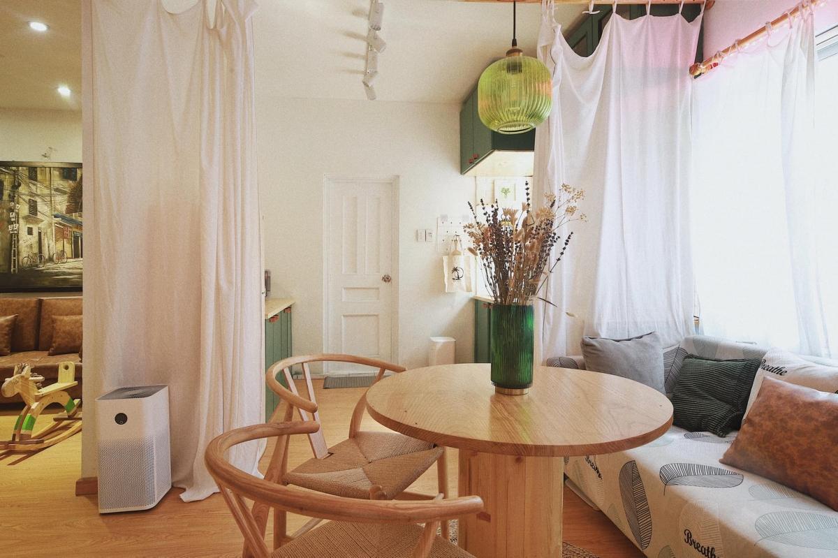 Phòng khách và phòng ngủ được ngăn cách bởi tấm rèm trắng, khiến nhà có cảm giác rộng rãi, thoáng đãng hơn.
