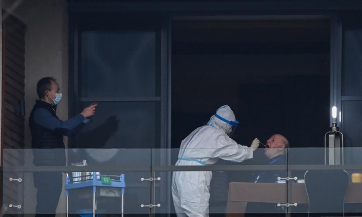 Nhân viên y tế lấy mẫu xét nghiệm Covid-19 cho thành viên nhóm điều tra của WHO tại Vũ Hán ngày 8/2. Ảnh: AFP.