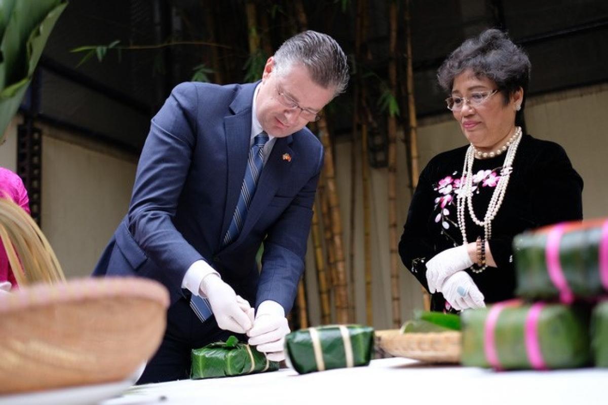 Đại sứ Mỹ Daniel Kritenbrink học gói bánh chưng với nghệ nhân Ánh Tuyết. Ảnh: Tùng Đinh/FB Đại sứ quán