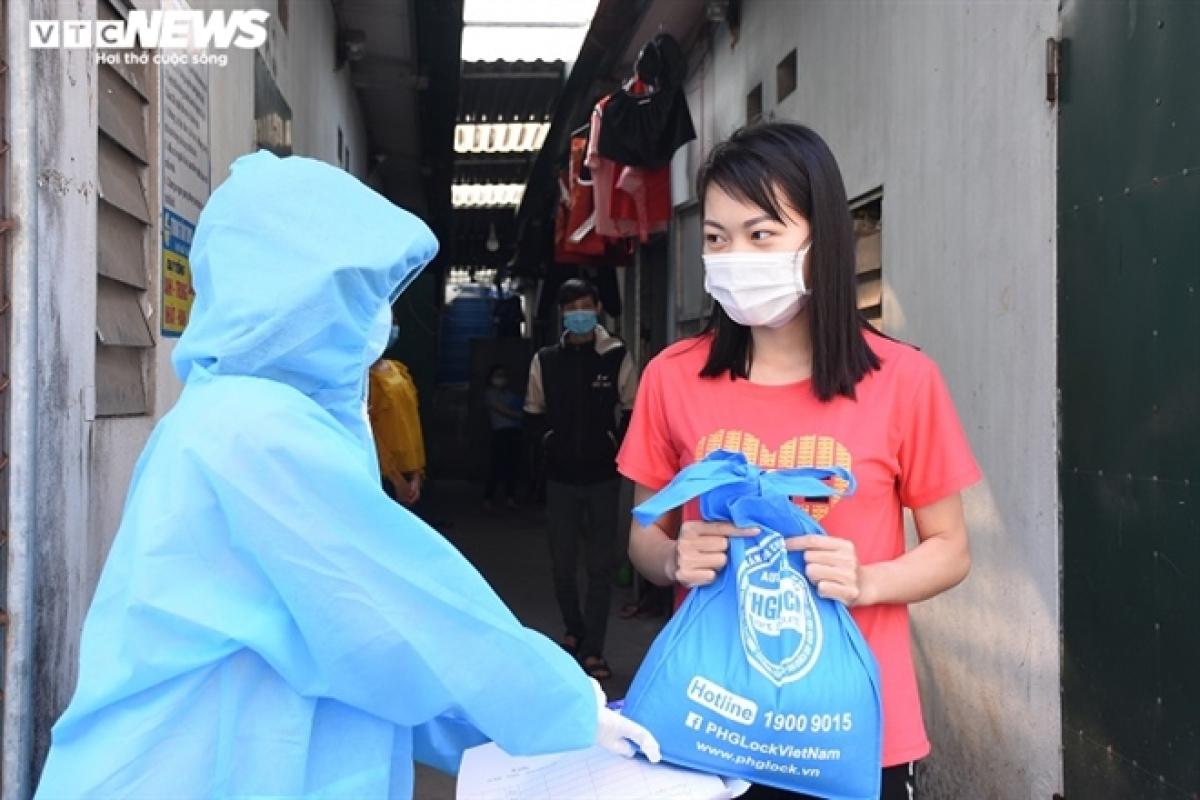 """Trong điều kiện dịch bệnh, nhiều khu vực ở huyện Cẩm Giàng phải cách ly, phong tỏa, mỗi công nhân đang thuê trọ sẽ nhận 5kg gạo được nhả từ cây """"ATM gạo"""" miễn phí tại ngay nơi mình thuê trọ."""