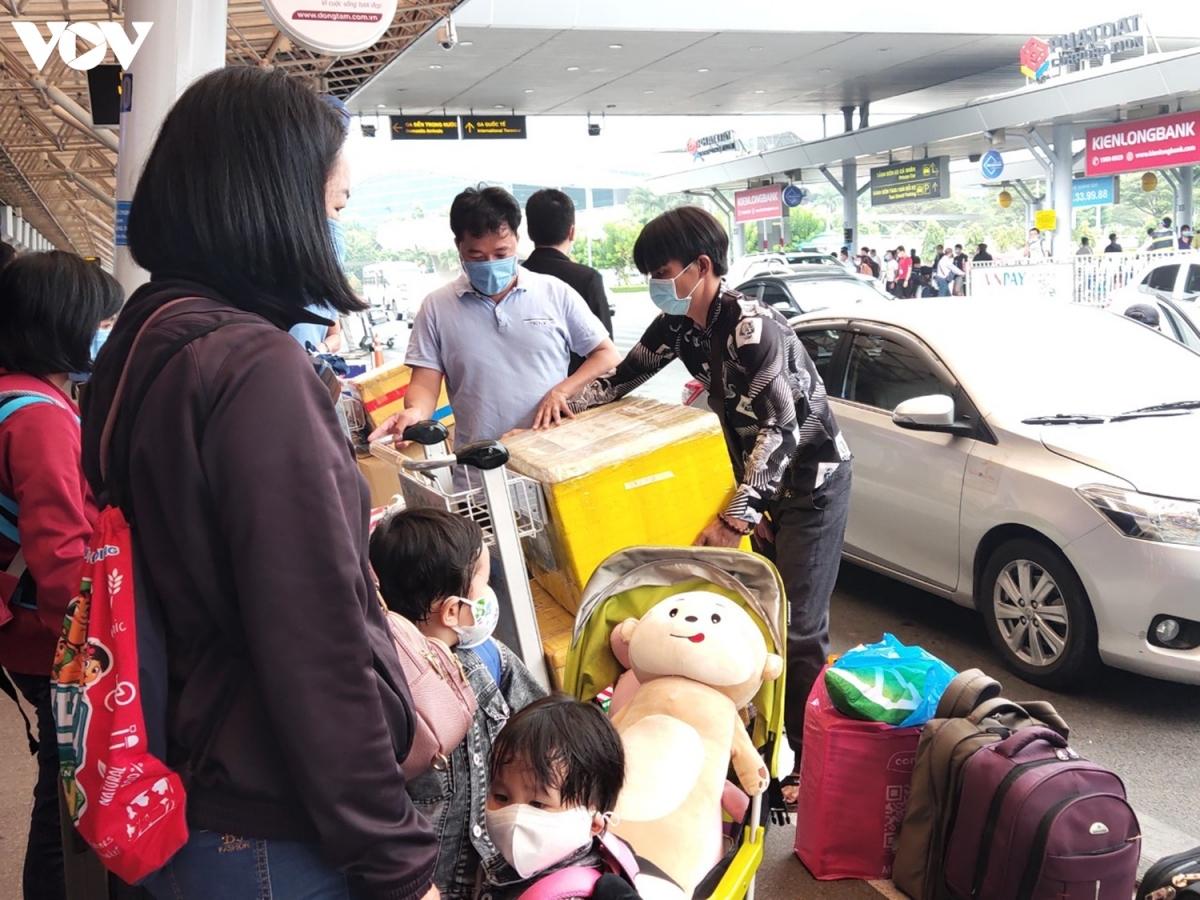 Một gia đình có con nhỏ đang tất bật chuyển đồ để kịp giờ bay.