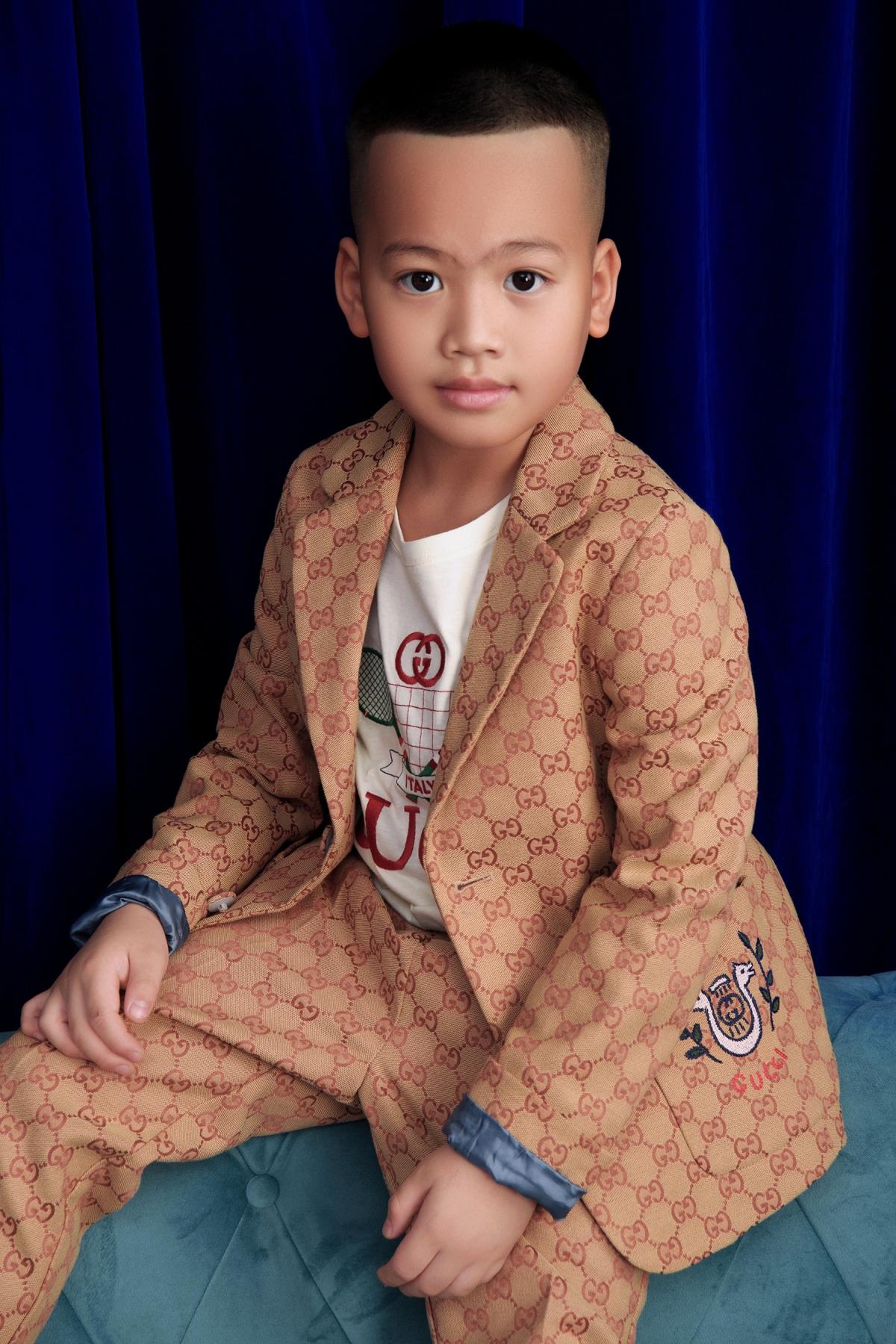 Tít (Đỗ Phạm Gia An) diện vest màu nâu nhạt phối cùng áo thun với hoạ tiết đặc trưng của thương hiệu Gucci. NTK tiết lộ con trai có thiên hướng trở thành người làm việc văn phòng, kinh doanh.