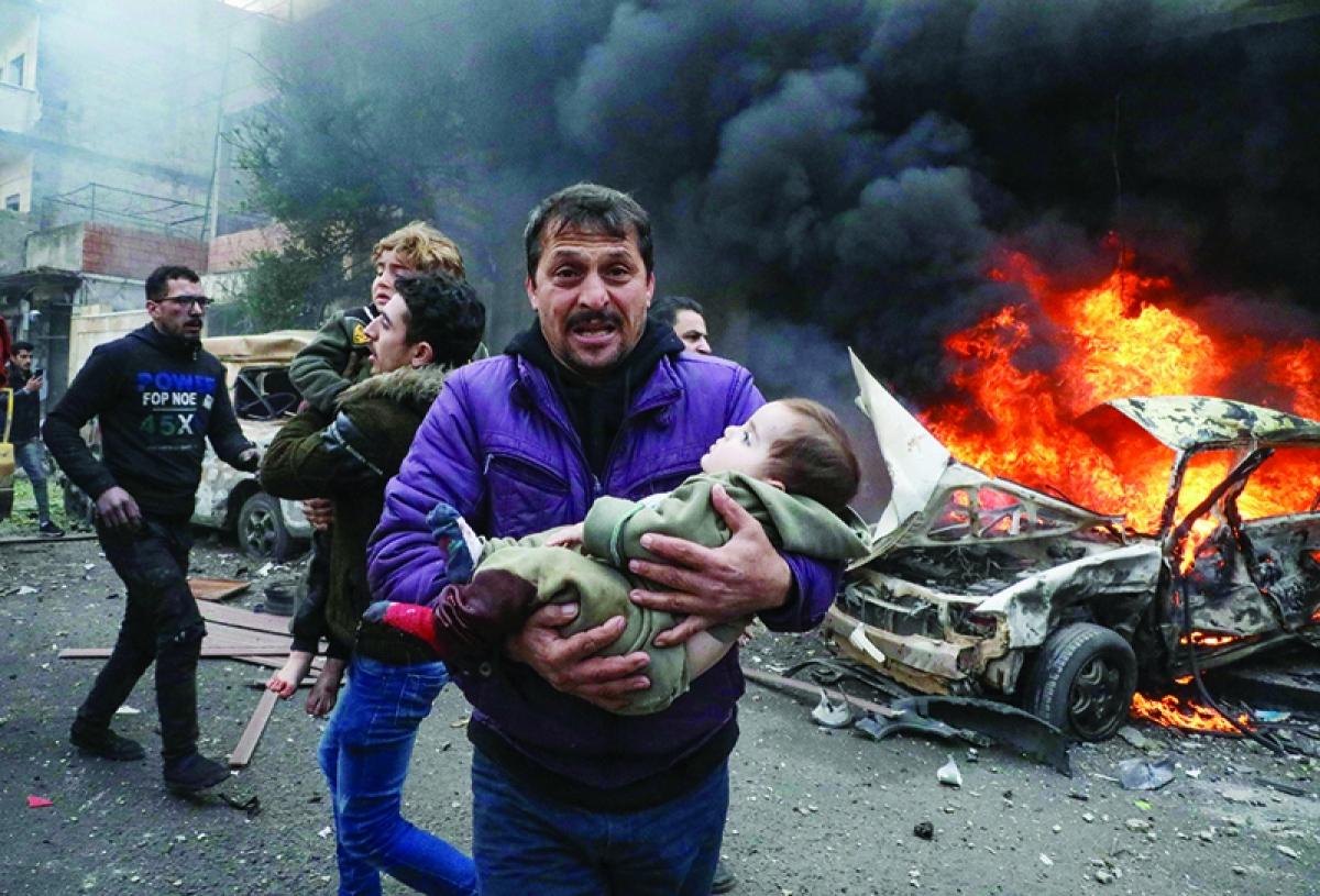Một người cha ôm đưa con nhỏ chạy khỏi hiện trường vụ đánh bom ở Aleppo. Ảnh: AFP