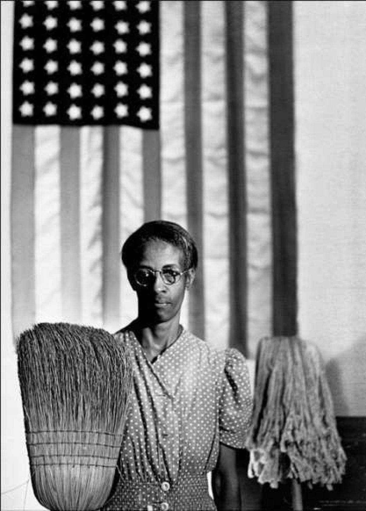 """Bức ảnh này ông Parks chụp đồng nghiệp tại Cục Quản lý An ninh Nông trại ở thủ đô Washington, với tạo dáng giống với bức tranh Grant Wood nổi tiếng """"American Gothic"""" của một người nông dân da trắng và vợ. Tuy nhiên, chủ đề trong bức ảnh của Parks là bà mẹ và người phụ nữ quét dọn da đen, Ella Watson, người quá bận rộn hoặc không có đủ thời gian để chỉnh sửa khuy trên váy."""