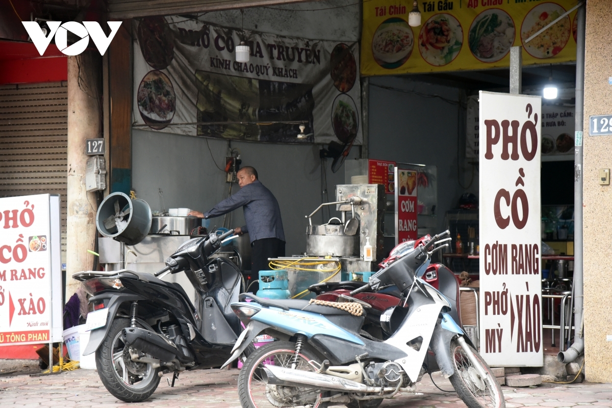 A shop selling pho (noodle soup) keeps its doors open on the morning of February 16