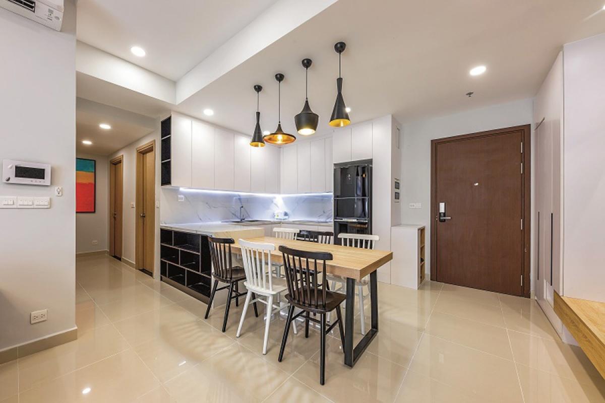 Để tiết kiệm không gian, bàn ăn được kê liền vào hệ thống tủ bếp, cũng là một ranh giới ngăn cách giữa khu bếp và phòng khách.