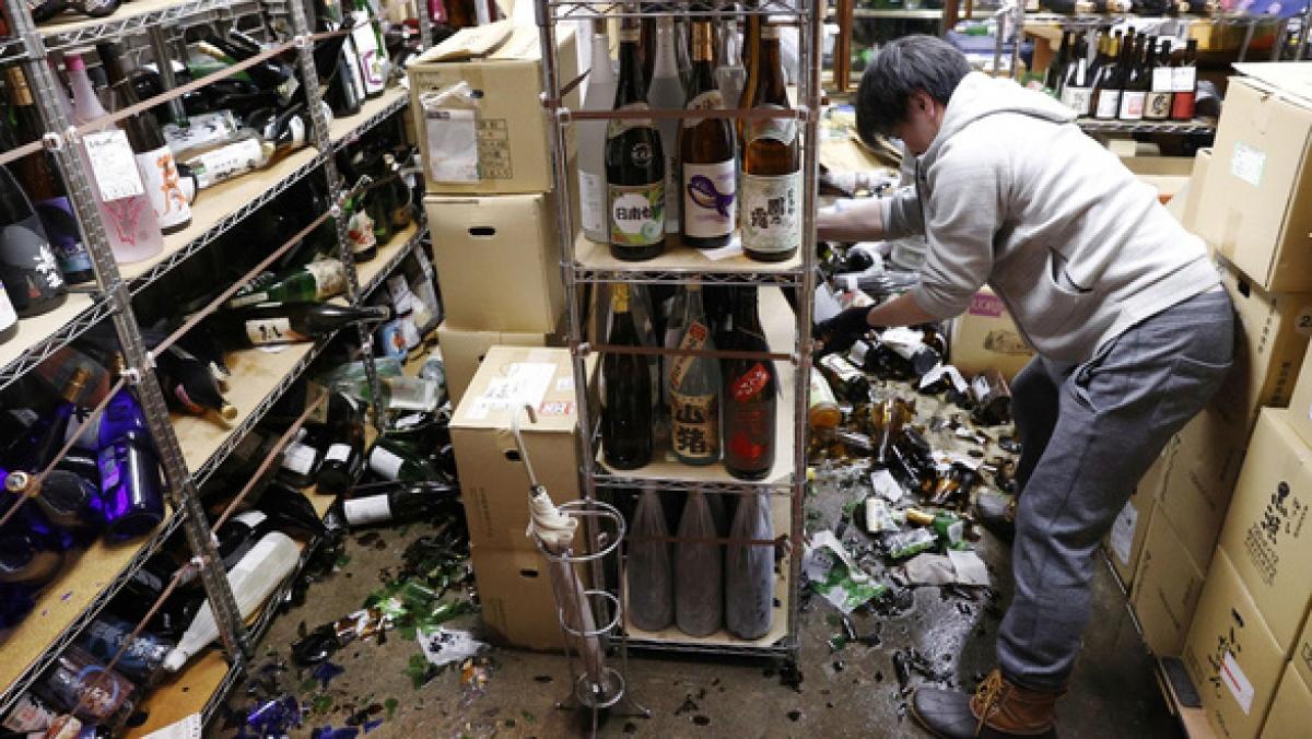 Một người dân Nhật Bản thu dọn đồ đạc bị đổ vỡ trong trận động đất tối 13-2 - Ảnh: REUTERS
