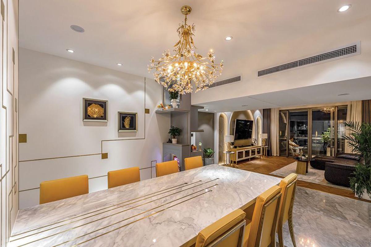 Khu vực bàn ăn được tạo điểm nhấn bằng bộ đèn chùm. Mặt bàn sử dụng chất liệu đá. Hầu hết các bề mặt như tường, mặt bàn, mặt tủ đều có những chi tiết trang trí sinh động.