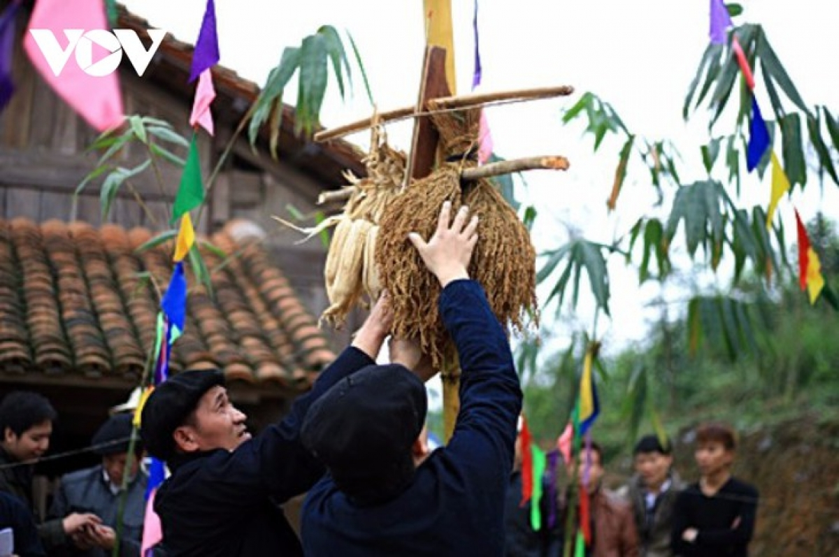 The village chief hangs a bottle of liquor and a sheaf of rice on the Neu pole.