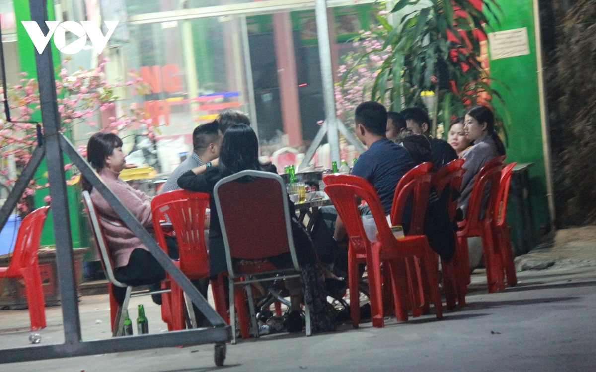 People gather at an outdoor restaurant with no social distancing whilst customers don't wear face masks on Nguyen Huu Tho street in Hoang Mai district.