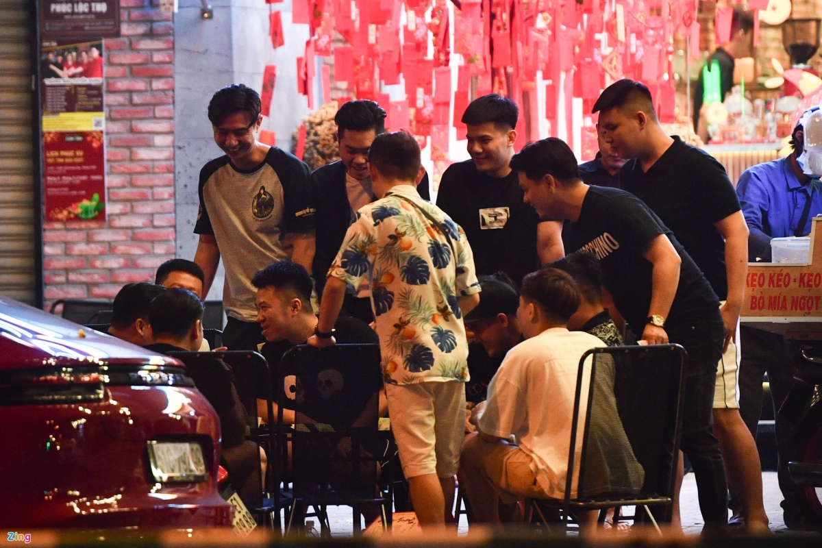A group of locals huddle together in front of a coffee shop on Quach Thi Trang street in District 1 at midnight on February 16.