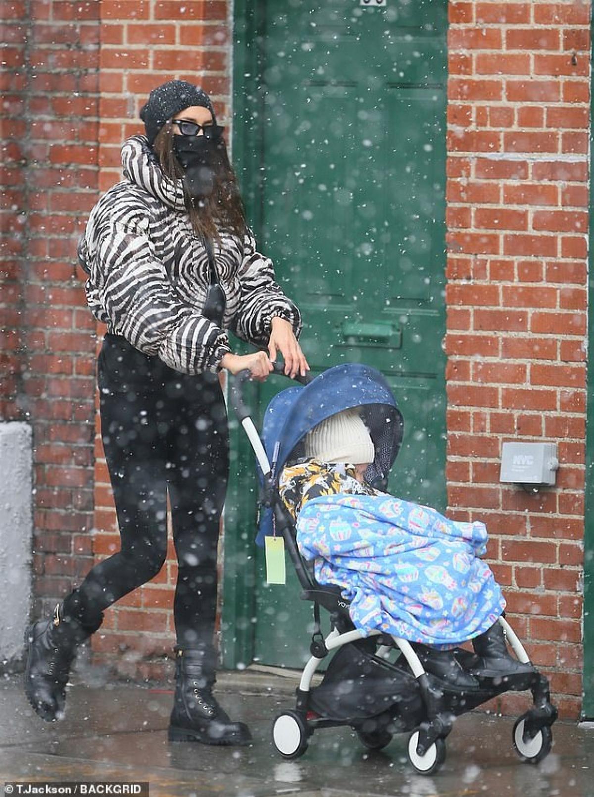 Bé Lea ngồi trong xe đẩy, mặc ấm áp và đắp thêm một chiếc chăn. Trong khi đó, Irina Shayk che chắn kín mít với áo choàng, mũ len và khẩu trang.