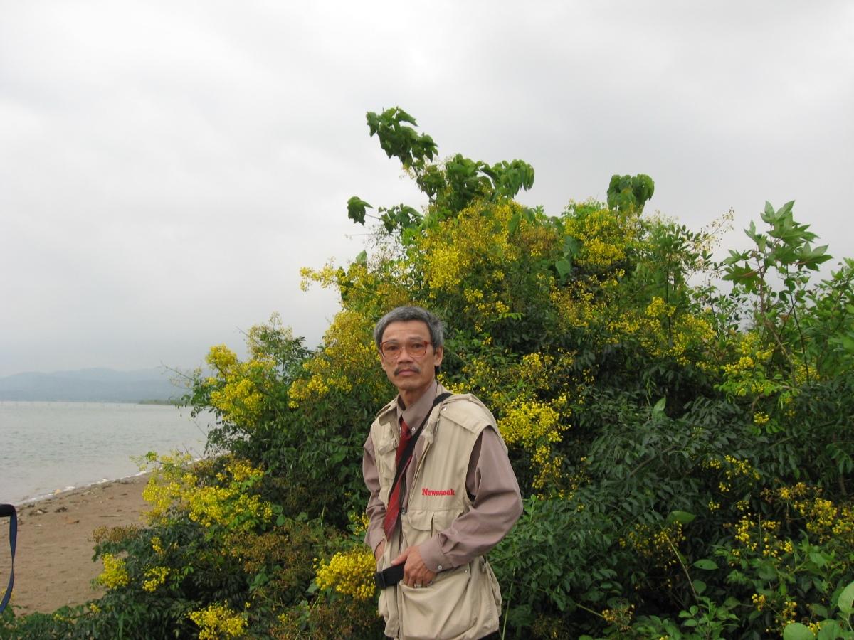 Nhà văn Nguyễn Thế Tường bên dòng Nhật Lệ và rặng hoa giêng giếng.