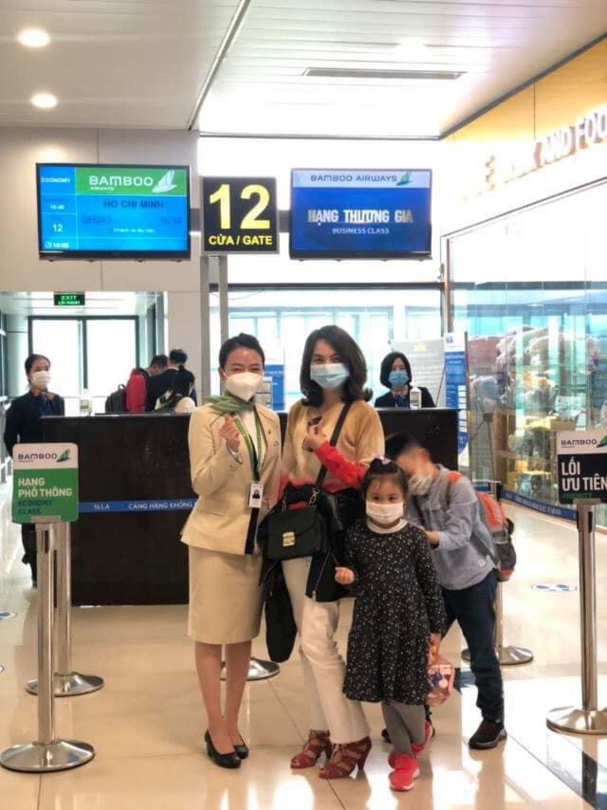 Ba mẹ con vui vẻ chụp ảnh lưu niệm cùng cô tiếp viên hàng không xinh đẹp trước khi lên máy bay về quê đón Tết.