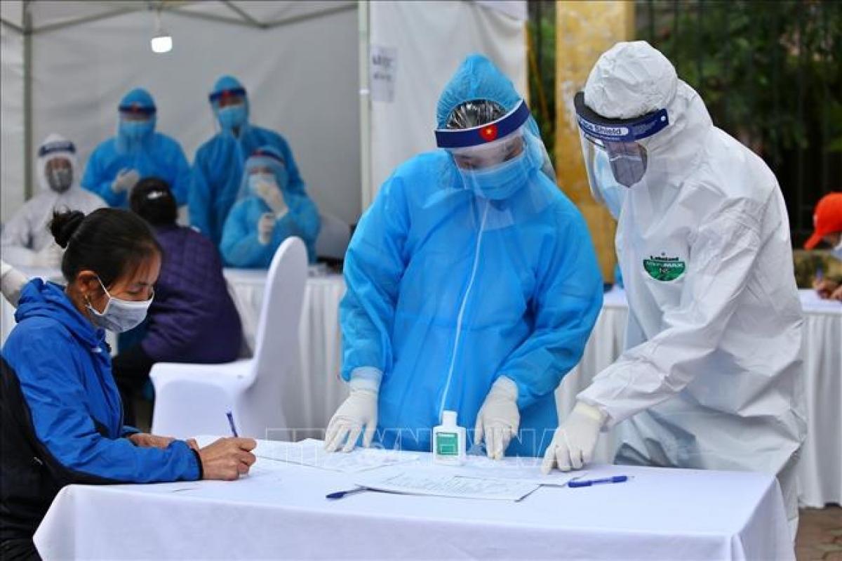 Nhân viên y tế hướng dẫn người dân khai vào tờ khai khi đến test nhanh Covid-19 ở Hà Nội. Ảnh: Minh Quyết/TTXVN.