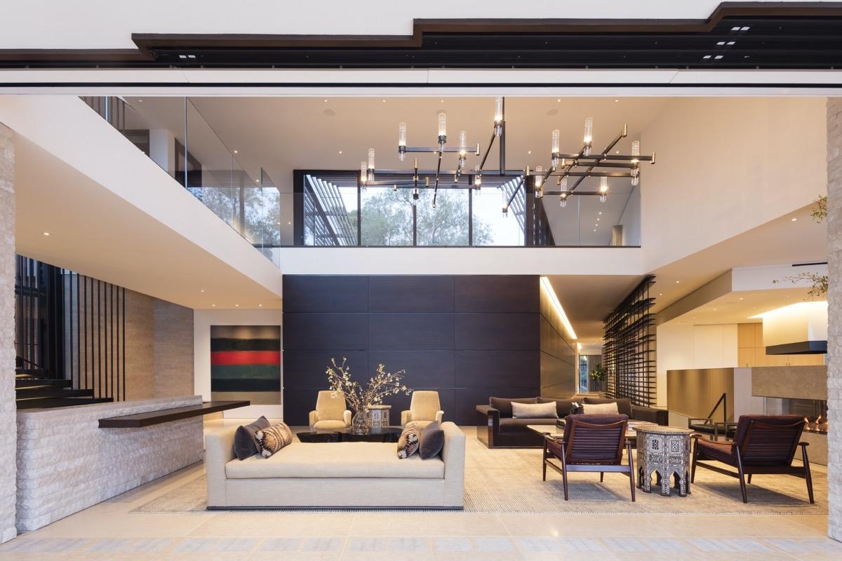 Kiến trúc sư sắp xếp một gác lửng nhỏ nằm ở tầng hai nhìn ra phòng khách sang trọng. Lan can kính đón ánh sáng mặt trời rực rỡ.