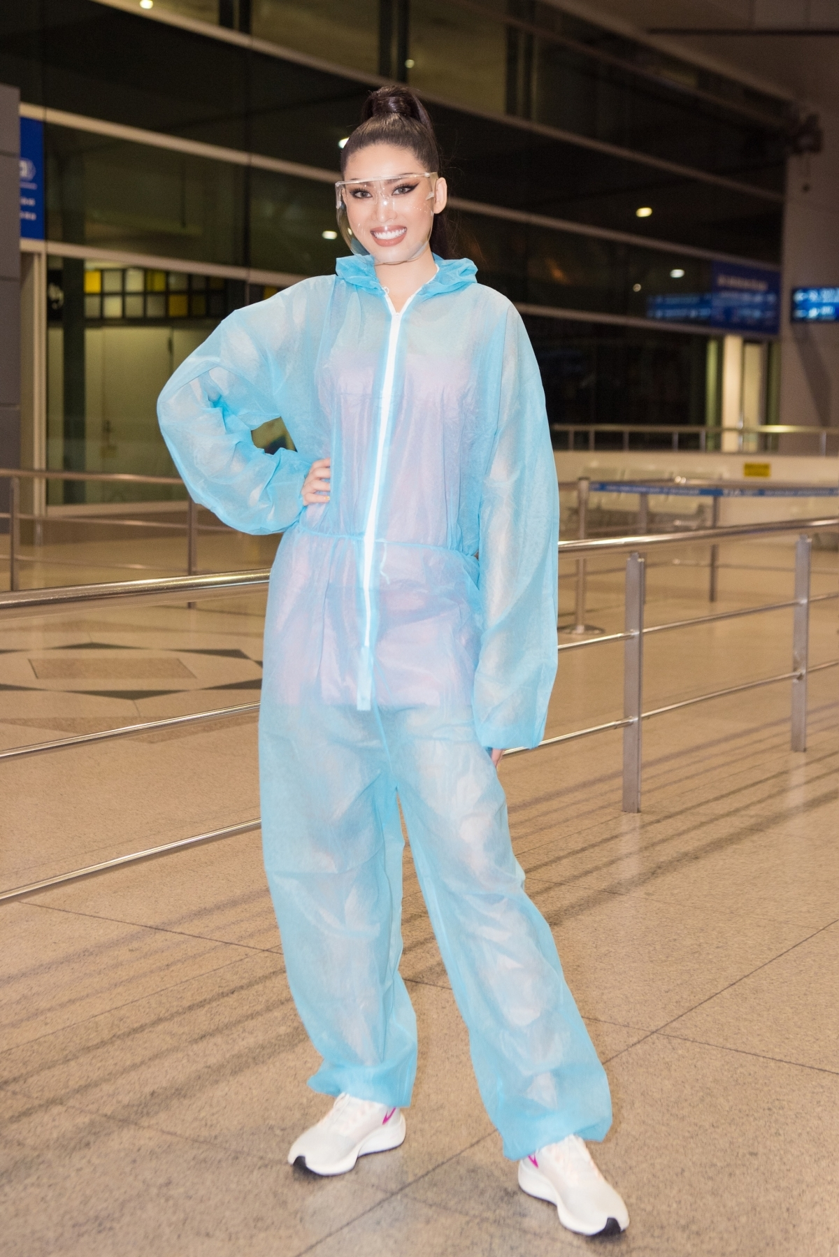 She strictly follows health recommendations against COVID-19 by wearing a personal protective suit before boarding the plane.