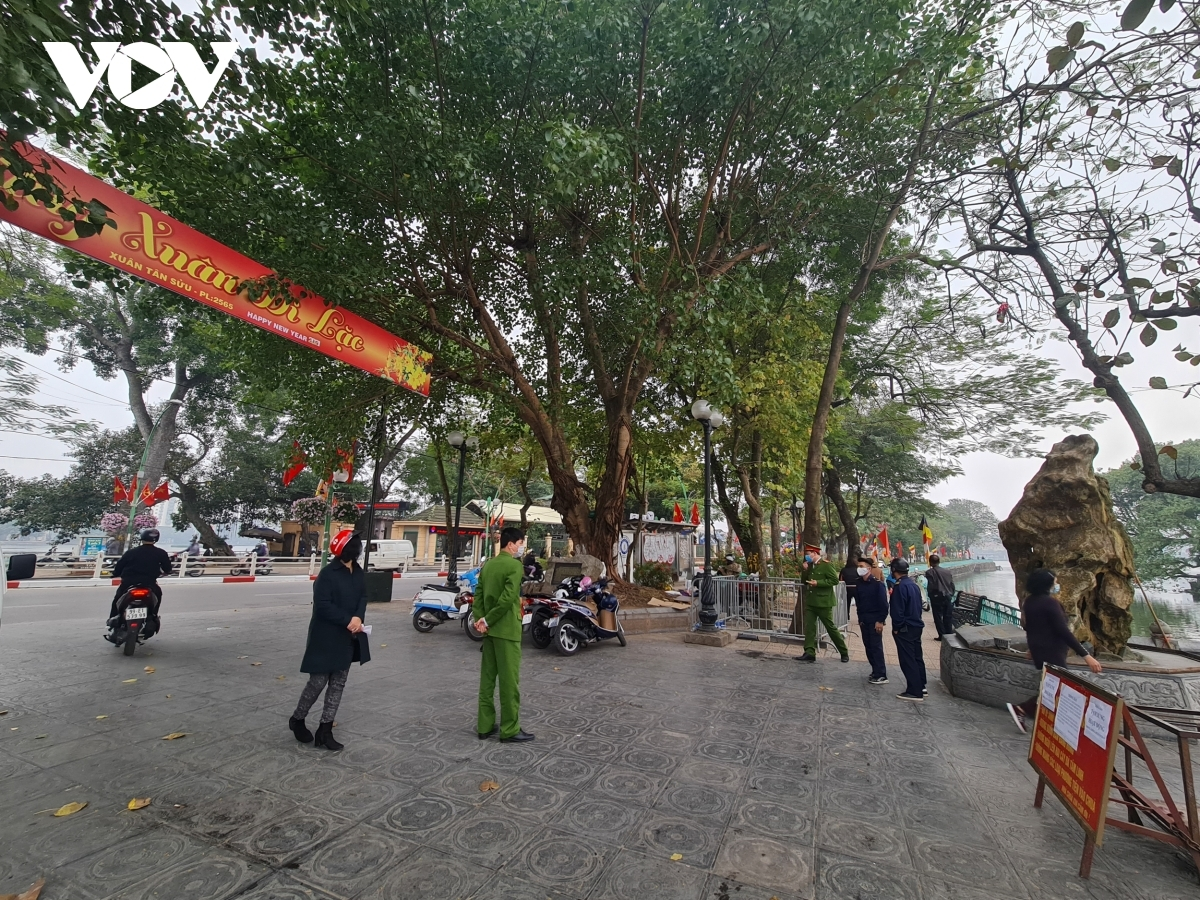 Policemen are on duty in order to warn people about not gatherings in front of Tran Quoc pagoda.