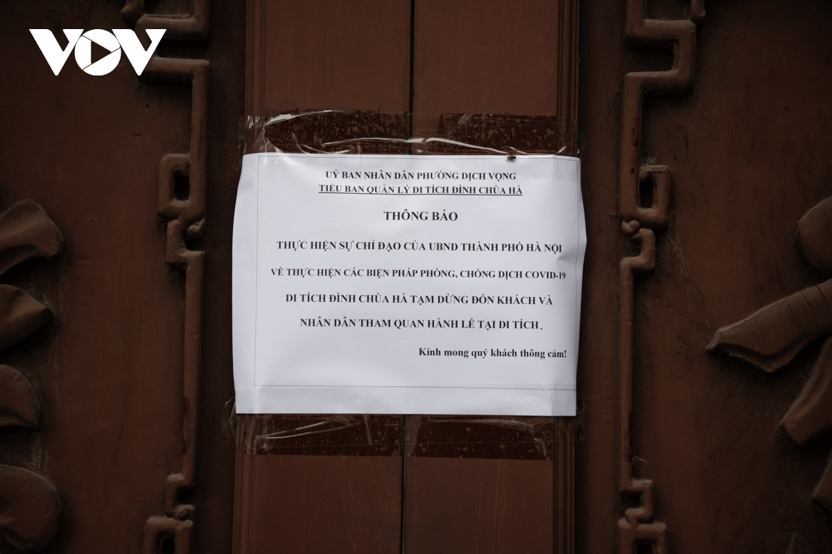 The management board of Ha pagoda places a notice on the door detailing their temporary closure as part of the COVID-19 fight.