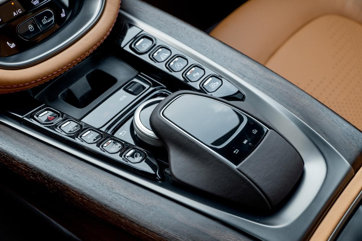 """SUV DBX còn được trang bị bệ tỳ tay trung tâm riêng biệt cho hai ghế ngồi, hộp đựng găng tay và vị trí đặt hệ thống điều khiển xe một cách thuận tiện. Là một phần của gói cá nhân hoá """"Q by Aston Martin"""" - bảng điều khiển trung tâm có thể được gia công từ các loại gỗ giá trị bậc nhất như Walnut."""